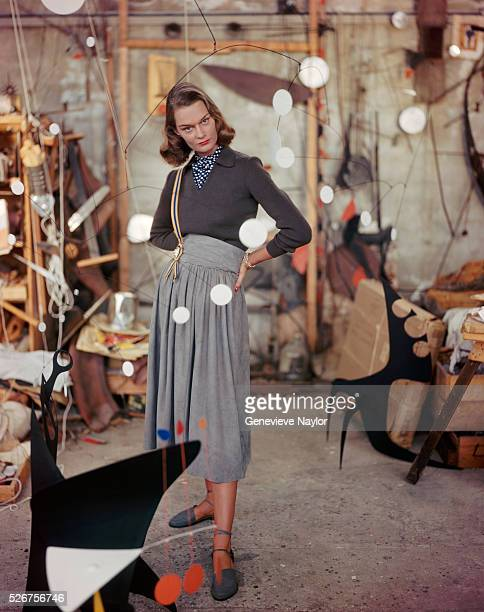 A woman models a gray suede skirt in the studio of artist Alexander Calder strolling among his mobiles