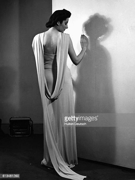 Woman models a halter neck evening dress by Motley, draped with a long scarf. England, 1934.