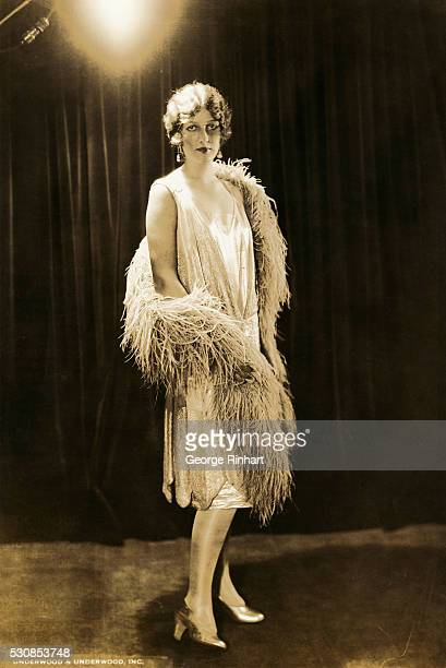 A woman models a loose fitting sleeveless dress and feather boa typical of the Flapper style of the 1920s