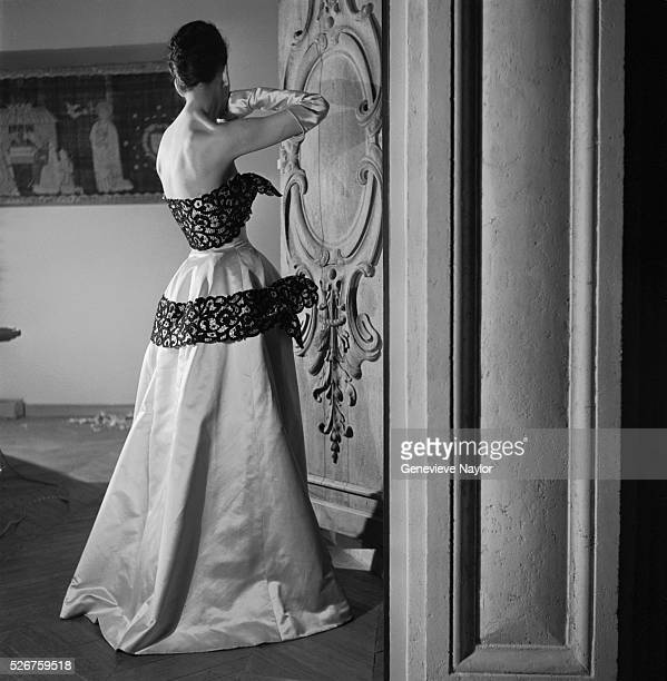A woman models a satin and lace ball gown