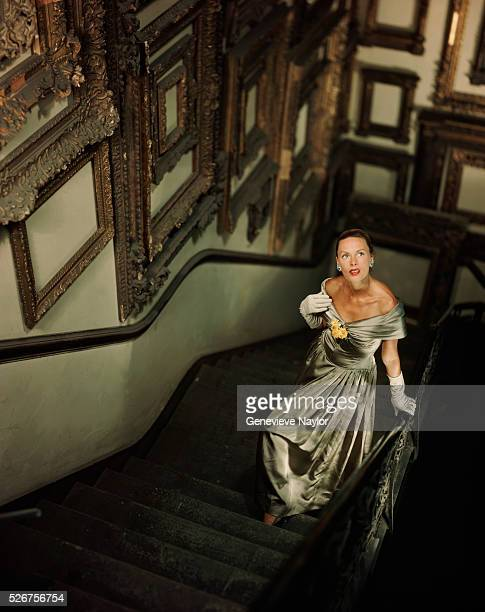 A woman models a silver evening dress by Pauline Trigere on a framing shop's stairway