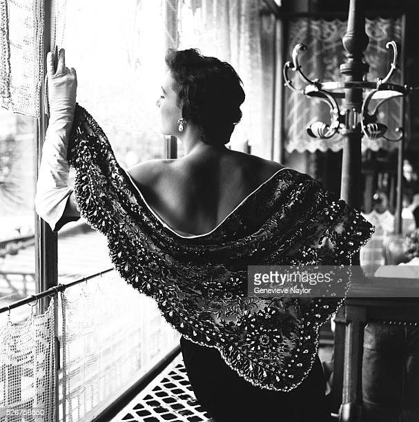 A woman models an ornately beaded shawl designed by Givenchy 1954