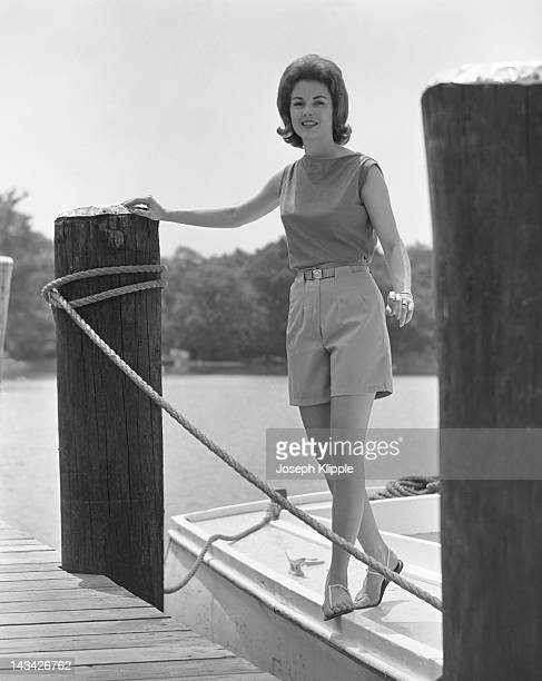 A woman models Bermuda shorts and a sleeveless top as she poses on a docked boat Washington DC June 28 1961