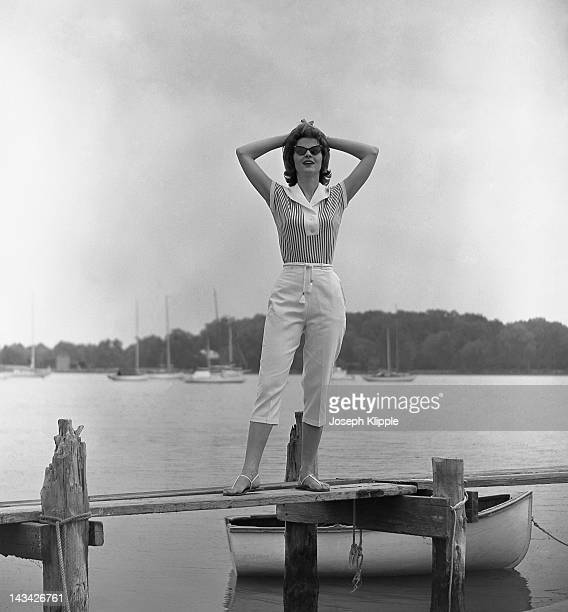 A woman models capri pants and a striped top as she poses with her hands on her head on a dock Washington DC June 28 1961