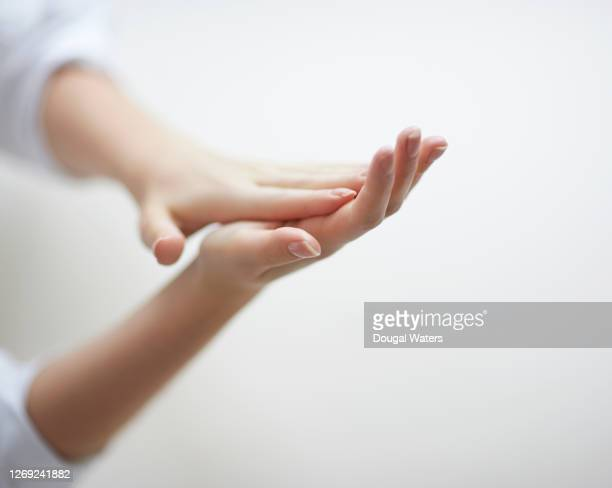 woman moisturising hands on white background, close up. - skin care stock pictures, royalty-free photos & images