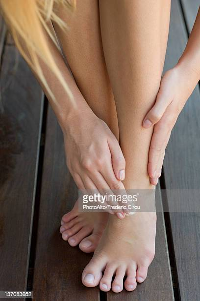 woman moisturizing feet, cropped - human foot stock photos and pictures