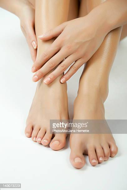 woman moisturizing feet, cropped - beautiful female feet stock photos and pictures