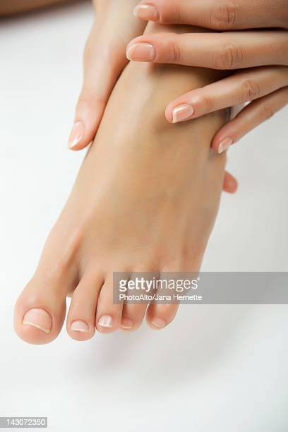 woman moisturizing foot, cropped - pretty toes and feet stock photos and pictures