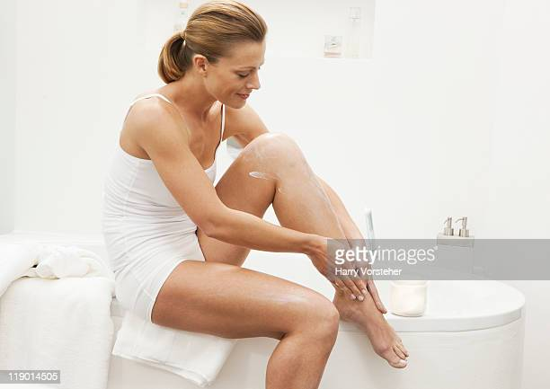 woman moisturizing her legs - leg stock pictures, royalty-free photos & images