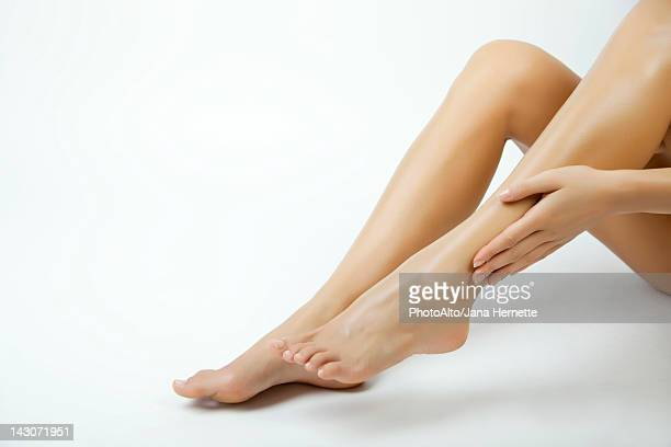 Woman moisturizing legs, cropped