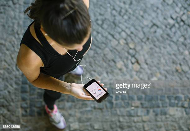 woman monitoring her workout progress on fitness app - mobile app stock pictures, royalty-free photos & images