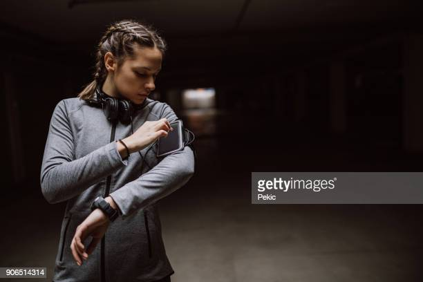woman monitoring her workout progress on fitness app - armband stock pictures, royalty-free photos & images