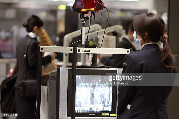 Woman monitors a thermal scanner as passengers from international flights walk by at Narita International Airport on April 29 2009 in Narita Japan...