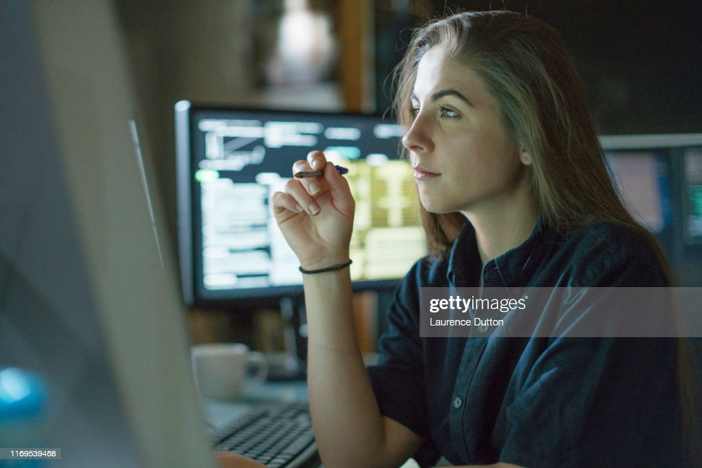 Woman monitors dark office : Stock Photo