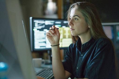 Woman monitors dark office 1169539468
