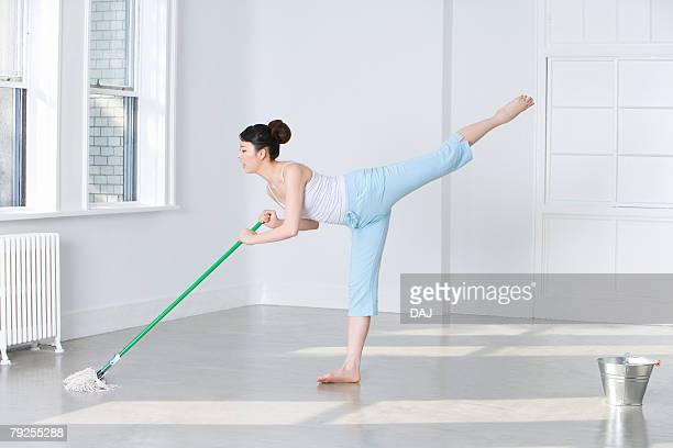 Woman mopping floor, standing on one leg
