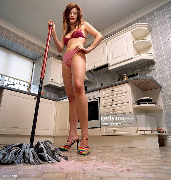 Woman mopping kitchen floor in underwear