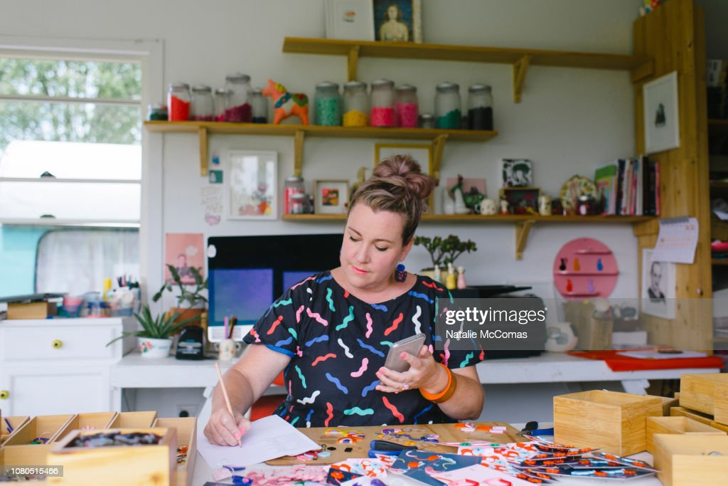 Mature adult female small business owner and designer working in studio office : Stock Photo