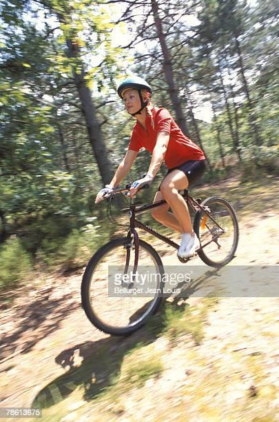 Woman mountain biking along trail