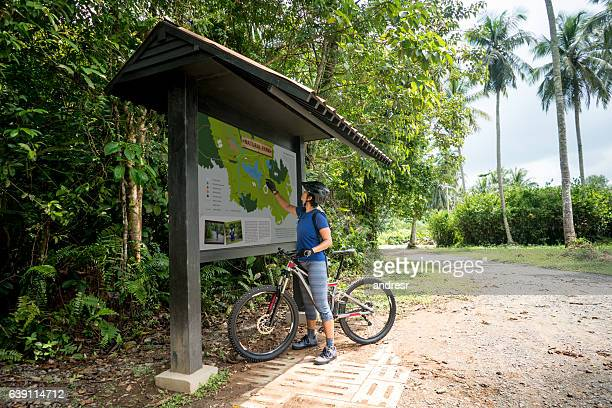 Woman mountain biking and looking at a map