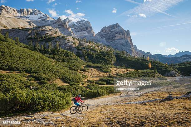 Woman mountain biking, Dolomites, South Tyrol, Italy