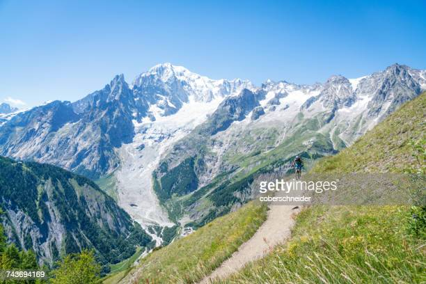woman mountain biking near mont blanc, aosta valley, switzerland - mont blanc massif stock photos and pictures