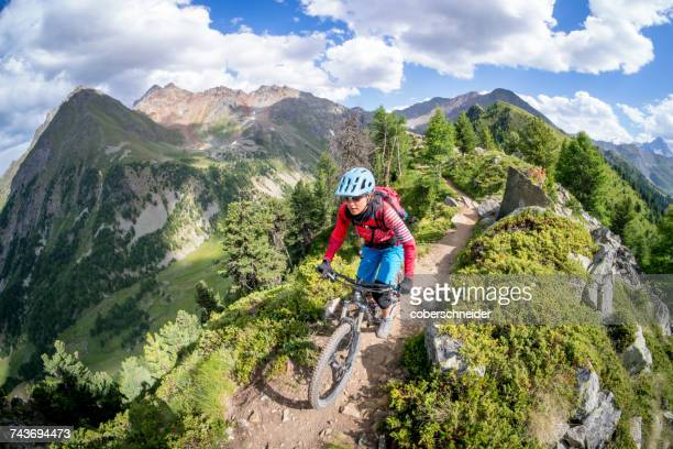 Woman Mountain Biking near Mont Blanc, Aosta Valley, Switzerland