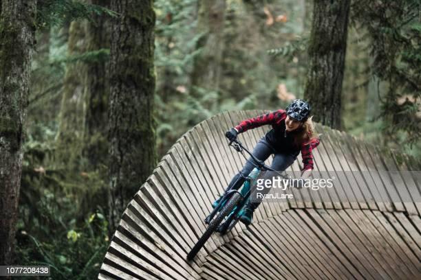 mujer ciclismo de montaña en senderos del bosque - tomar una curva deporte fotografías e imágenes de stock