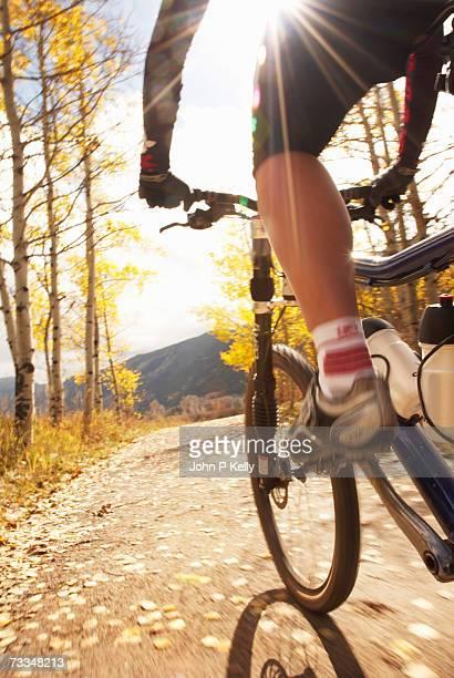 woman mountain biking on road, smiling, low section - guidom - fotografias e filmes do acervo