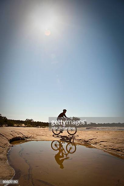 A woman mountain biking on slickrock in front of pool near Hurricane, Utah.