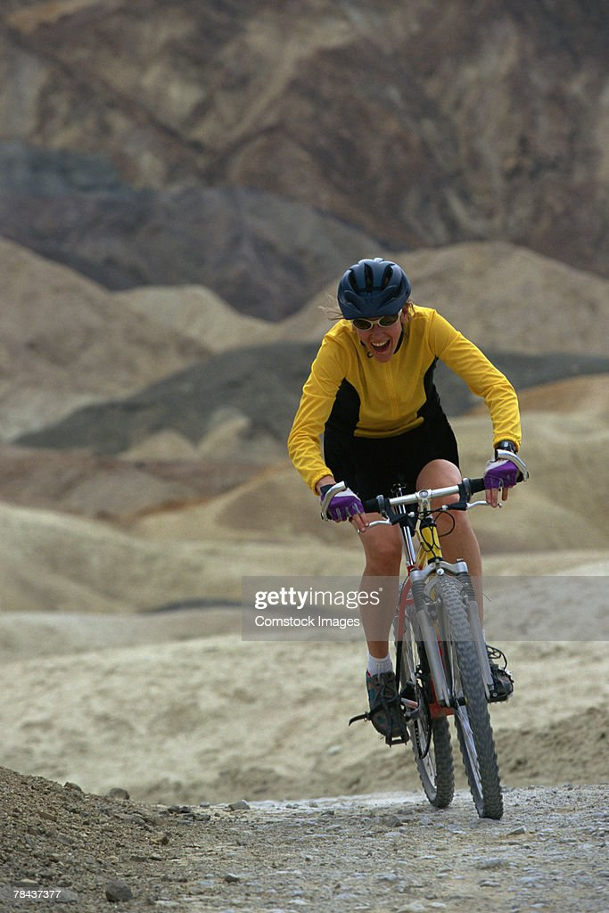 Woman mountain biking : Stock Photo