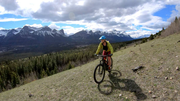 Woman mountain e-bikes up a grassy alpine meadow above the valley