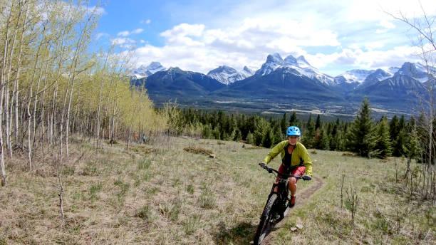 Woman mountain e-bikes up a steep and narrow trail along an alpine meadow