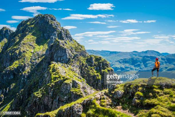 woman mountaineer looking back along rocky mountain ridge summer sunshine - mountaineering stock pictures, royalty-free photos & images