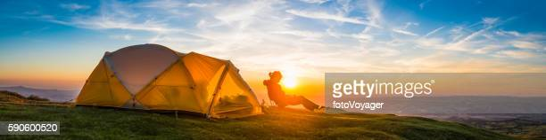 Woman mountaineer relaxing beside tent idyllic summer sunset camping panorama