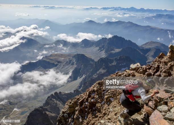 女性登山家は山の斜面をスクランブル - スクランブリング ストックフォトと画像