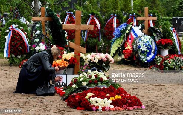 A woman mourns after a funeral ceremony at a cemetery in Saint Petersburg on July 6 three days after a fire that killed 14 officers on what was...