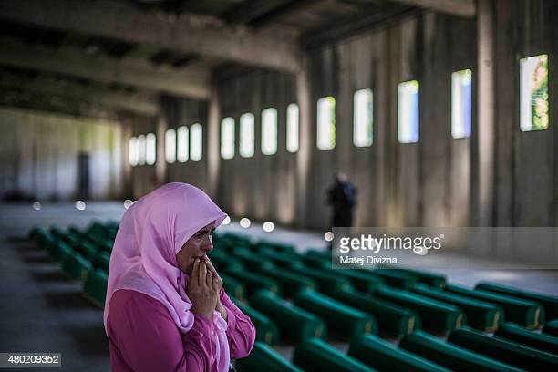 A woman mourns among 136 coffins of victims of the 1995 Srebrenica massacre in the hall at the Potocari cemetery and memorial near Srebrenica on July...
