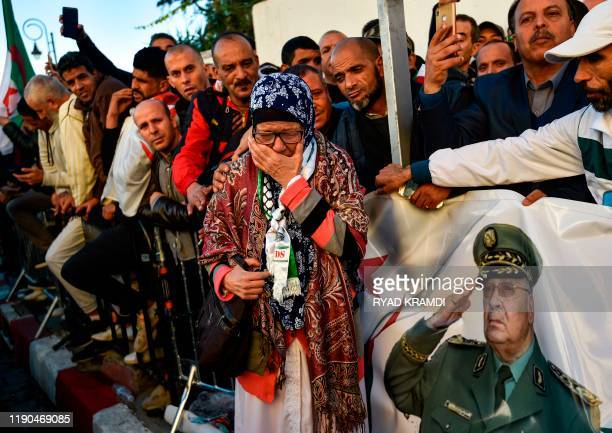 A woman mourns as she gathers with other people outside the Palais du Peuple during the funeral of Algeria's late military chief Lieutenant general...