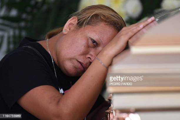 TOPSHOT A woman mourns as she leans against the coffin of a victim of the attack at the Caballo Blanco bar during a funeral service at a cemetery in...