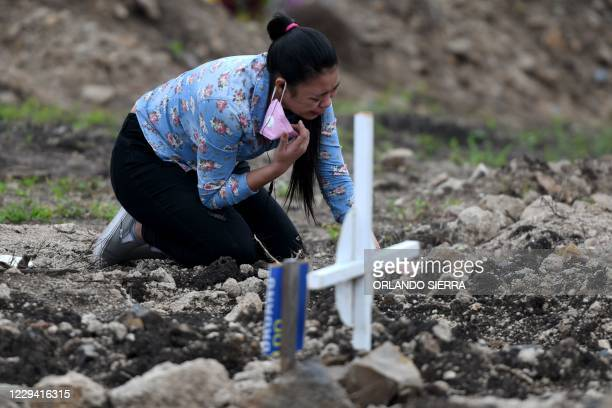 """Woman mourns by the grave of her grandmother, victim of the new coronavirus pandemic, in the cemetery """"Covid-19"""", on the Day of the Dead, in..."""