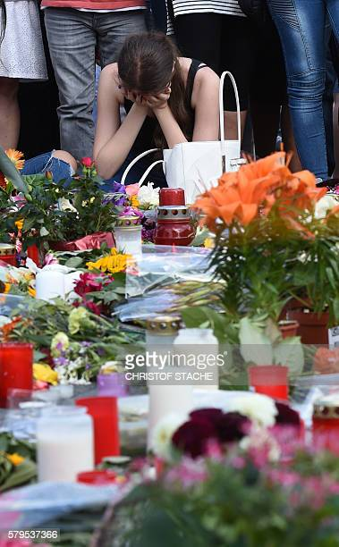A woman mourns in front of candles and flowers on July 24 2016 in front of the Olympia Einkaufszentrum shopping centre in Munich southern Germany...