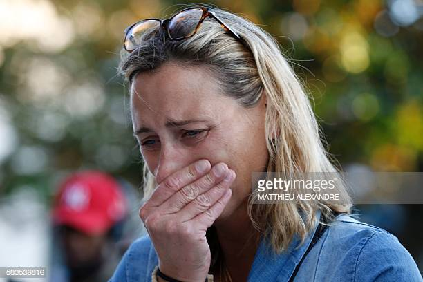 A woman mourns in front of the city hall in the Normandy city of SaintEtienneduRouvray on July 26 after a priest was killed in the latest of a string...