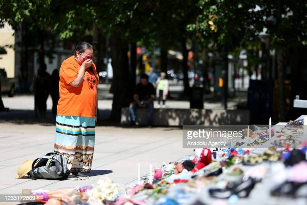 Woman mourns over 215 pairs of kids shoes outside Vancouver Art Gallery during a memorial on May 29, 2021 in Vancouver, British Columbia, Canada The...