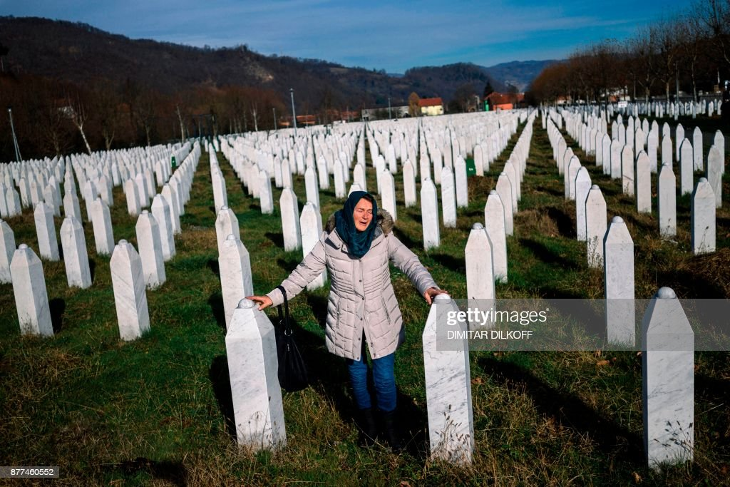 TOPSHOT - A woman mourns over a relative's grave at the memorial centre of Potocari near Srebrenica on November 22, 2017. United Nations judges on November 22, 2017 sentenced former Bosnian Serbian commander Ratko Mladic to life imprisonment after finding him guilty of genocide and war crimes in the brutal Balkans conflicts over two decades ago. PHOTO / Dimitar DILKOFF