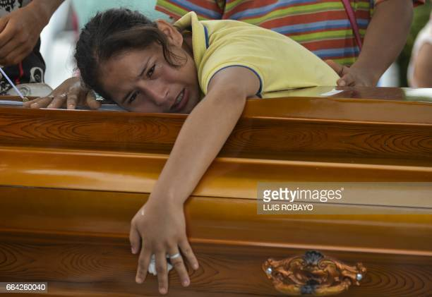 TOPSHOT A woman mourns over the coffin of her father killed by a mudslide caused by heavy rains at the cemetery in Mocoa Putumayo department Colombia...