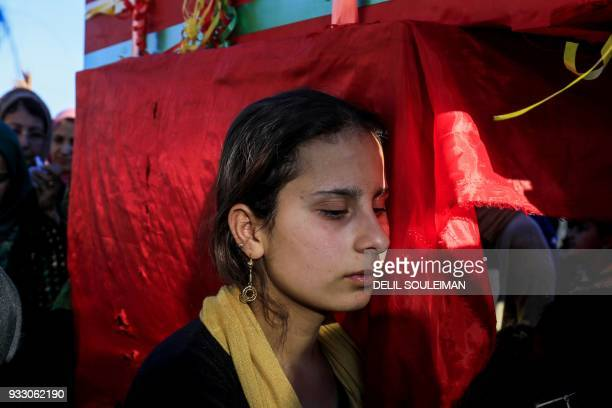 TOPSHOT A woman mourns while standing next to a coffin during the funeral of People's Protection Units fighters in the northeastern Syrian city of...