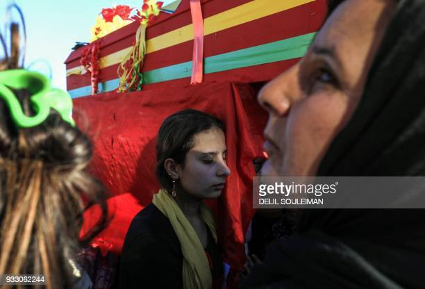 A woman mourns while standing next to a coffin during the funeral of People's Protection Units fighters in the northeastern Syrian city of Qamishli...