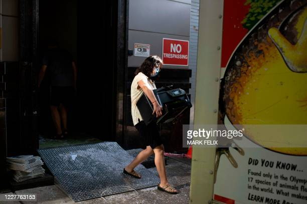 Woman moves equipment into a U-Haul truck at the Chinese consulate in Houston on July 24 after the US State Department ordered China to close the...