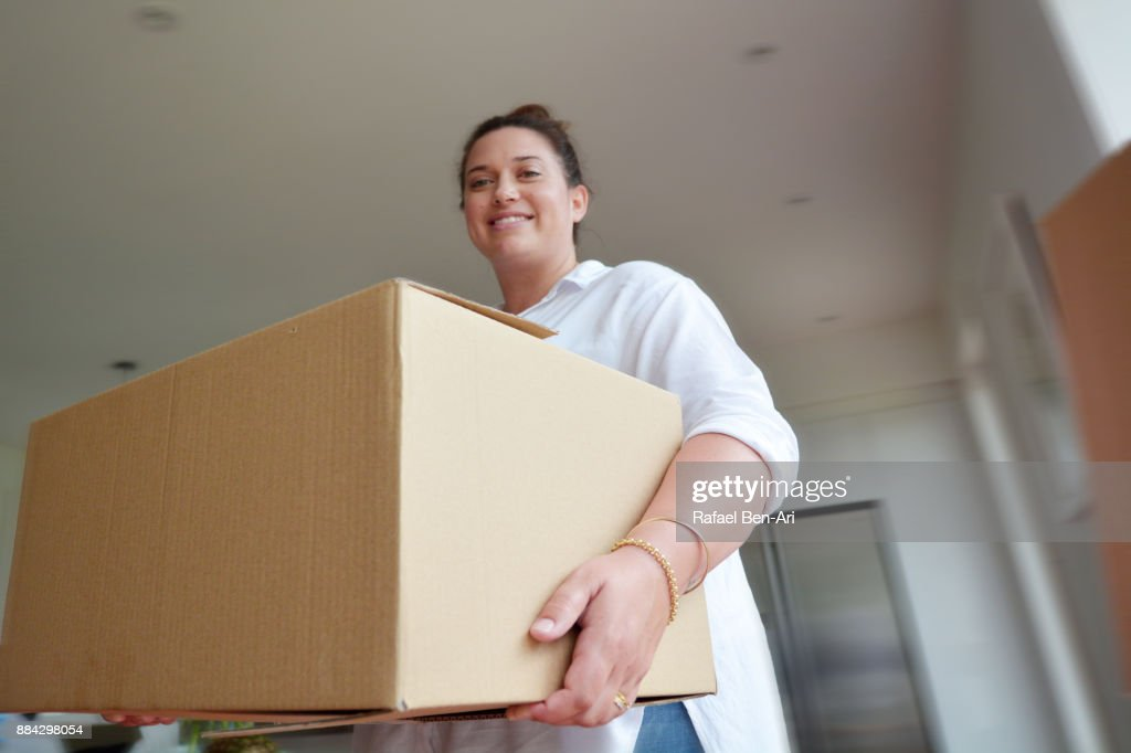 Woman moves into her new home : Stock Photo